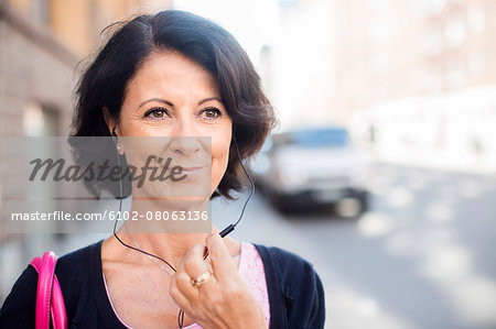 Smiling mature woman with earphones Stock Photo - Premium Royalty-Free, Image code: 6102-08063136