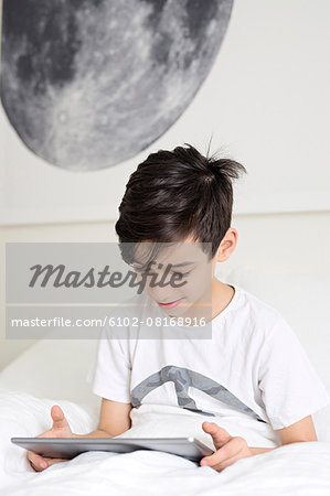 Boy in bed with digital tablet Stock Photo - Premium Royalty-Free, Image code: 6102-08168916