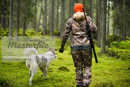 Woman with hunting dog in forest Stock Photo - Premium Royalty-Free, Image code: 6102-08184083