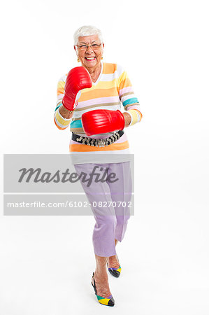 Smiling senior woman wearing boxing gloves Stock Photo - Premium Royalty-Free, Image code: 6102-08270702