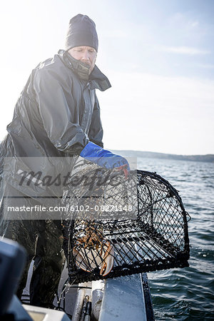 Fisherman with lobster trap Stock Photo - Premium Royalty-Free, Image code: 6102-08271148
