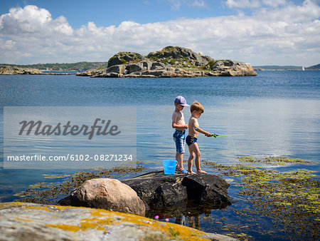 Boys fishing at sea Stock Photo - Premium Royalty-Free, Image code: 6102-08271234