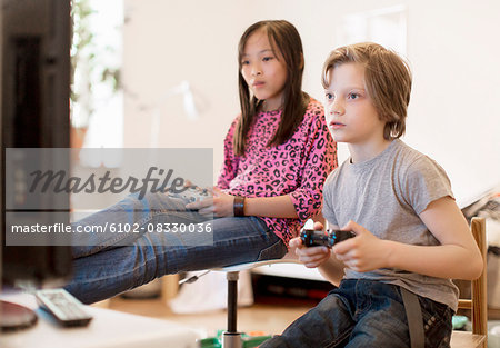 Boy and girl playing video game Stock Photo - Premium Royalty-Free, Image code: 6102-08330036