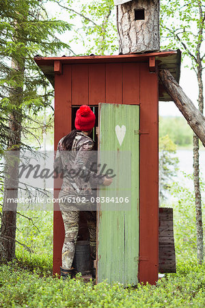 Woman entering wooden outhouse Stock Photo - Premium Royalty-Free, Image code: 6102-08384106