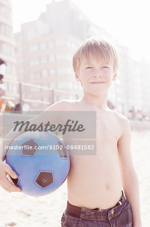Young boy holding volleyball on beach Stock Photo - Premium Royalty-Free, Image code: 6102-08481582
