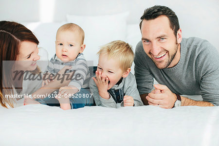 Parents with two small kids playing in bedroom Stock Photo - Premium Royalty-Free, Image code: 6102-08520807
