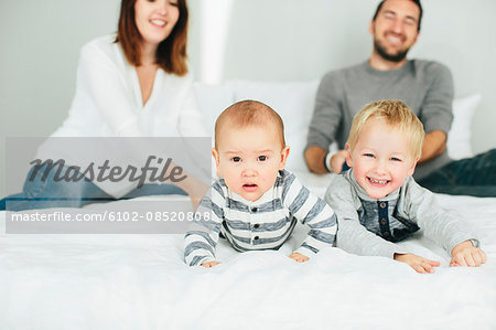 Parents with two small kids playing in bedroom Stock Photo - Premium Royalty-Free, Image code: 6102-08520808
