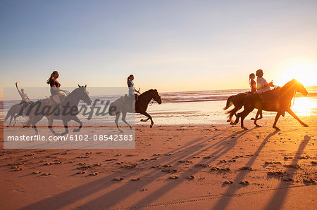 Group of people horseback riding on beach at sunset Stock Photo - Premium Royalty-Free, Image code: 6102-08542383