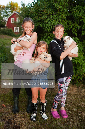 Portrait of three girls holding pets Stock Photo - Premium Royalty-Free, Image code: 6102-08558793