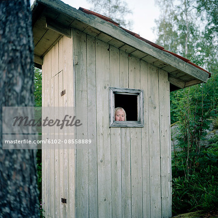 Girl in outhouse Stock Photo - Premium Royalty-Free, Image code: 6102-08558889