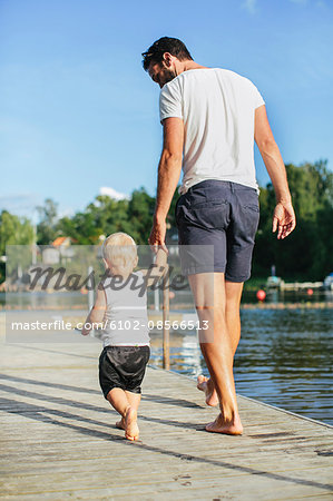 Father with walking on jetty Stock Photo - Premium Royalty-Free, Image code: 6102-08566513