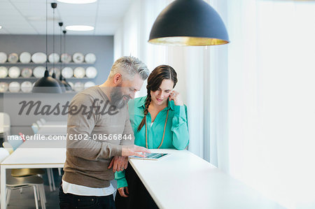 Colleagues using tablet Stock Photo - Premium Royalty-Free, Image code: 6102-08566844
