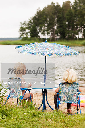 Little kids sitting on chair at beach Stock Photo - Premium Royalty-Free, Image code: 6102-08746639