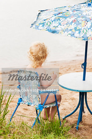 Little boy sitting on chair at beach Stock Photo - Premium Royalty-Free, Image code: 6102-08746640
