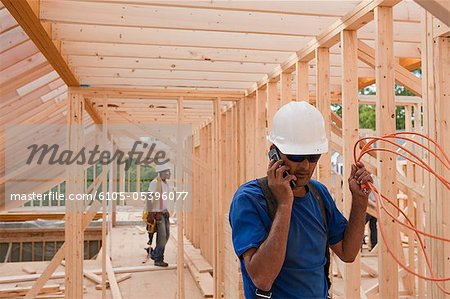 Carpenter holding power cord and talking on mobile phone Stock Photo - Premium Royalty-Free, Image code: 6105-05396077