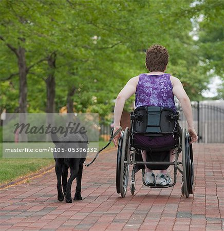 Woman with multiple sclerosis in a park with a service dog Stock Photo - Premium Royalty-Free, Image code: 6105-05396332