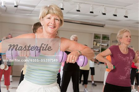 Senior exercise class working with dumbbells Stock Photo - Premium Royalty-Free, Image code: 6105-05397149