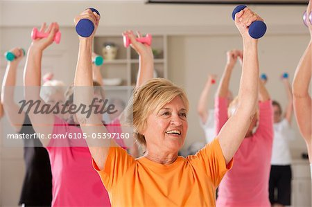 Seniors exercising with dumbbells in a health club Stock Photo - Premium Royalty-Free, Image code: 6105-05397160