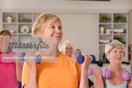 People exercising with dumbbells in a health club Stock Photo - Premium Royalty-Free, Image code: 6105-05397161