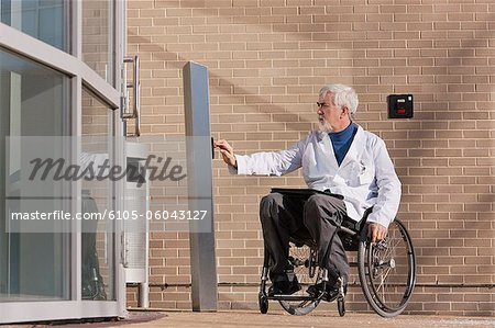 Doctor with muscular dystrophy in wheelchair at hospital entrance pressing knob for accessible door Stock Photo - Premium Royalty-Free, Image code: 6105-06043127
