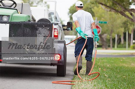 Pest control technician with high pressure spray gun and hose at his truck Stock Photo - Premium Royalty-Free, Image code: 6105-06702853