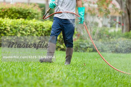 Pest control technician using high pressure spray gun and hose with heavy duty gloves Stock Photo - Premium Royalty-Free, Image code: 6105-06702854