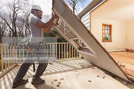 Hispanic carpenter removing newly cut door access to deck on home Stock Photo - Premium Royalty-Free, Image code: 6105-06702951