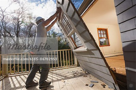Hispanic carpenter removing newly cut door access to deck on home Stock Photo - Premium Royalty-Free, Image code: 6105-06702953