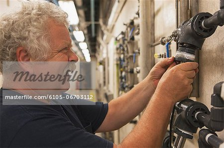 Engineer putting a rebuilt O2 electrochemical sensor probe into service on piping in water treatment plant Stock Photo - Premium Royalty-Free, Image code: 6105-06703112