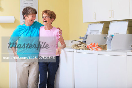 Senior women laughing in a laundry room Stock Photo - Premium Royalty-Free, Image code: 6105-07521343
