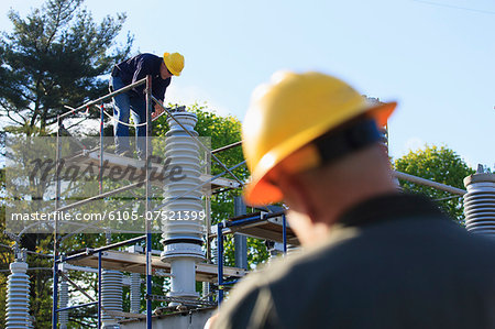 Power engineer performing maintenance on fluid filled high voltage insulator, Braintree, Massachusetts, USA Stock Photo - Premium Royalty-Free, Image code: 6105-07521399