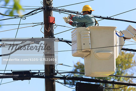 Power engineer in lift bucket working on power lines, Braintree, Massachusetts, USA Stock Photo - Premium Royalty-Free, Image code: 6105-07521406
