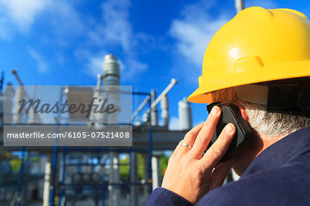 Power engineer talking on a mobile phone at high voltage distribution station, Braintree, Massachusetts, USA Stock Photo - Premium Royalty-Free, Image code: 6105-07521408