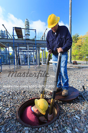 Power engineer entering manhole at a high voltage power distribution station, Braintree, Massachusetts, USA Stock Photo - Premium Royalty-Free, Image code: 6105-07521410