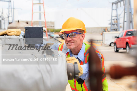 Electrical engineer examining pressure sensor at an electric power plant Stock Photo - Premium Royalty-Free, Image code: 6105-07521453