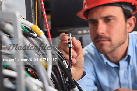 Network engineer holding BNC cable connection at patch panel Stock Photo - Premium Royalty-Free, Image code: 6105-07744487