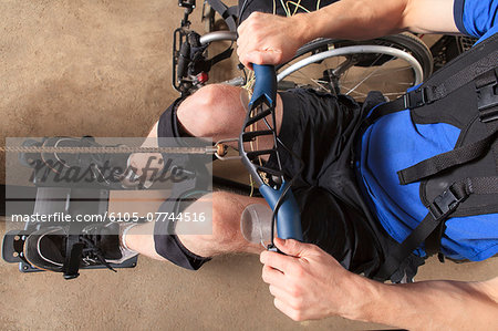 Man with spinal cord injury using his rowing machine with a muscle stimulator attached Stock Photo - Premium Royalty-Free, Image code: 6105-07744516