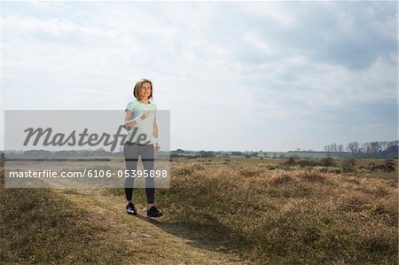 Woman power walking with mp3 player Stock Photo - Premium Royalty-Free, Image code: 6106-05395898