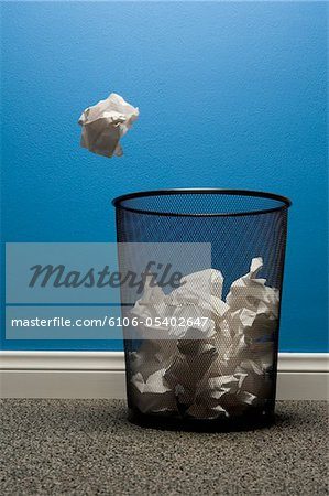 Crumpled paper about to fall into waste basket Stock Photo - Premium Royalty-Free, Image code: 6106-05402647
