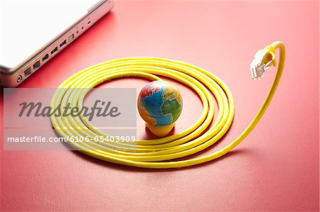 Yellow LAN cable and a globe. Stock Photo - Premium Royalty-Free, Image code: 6106-05403909