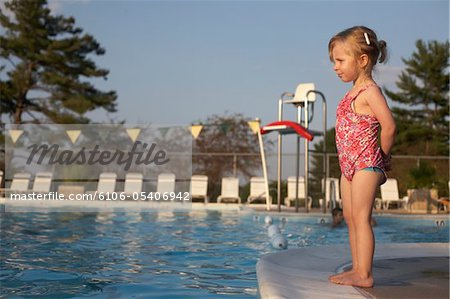 Young girl standing at edge of pool Stock Photo - Premium Royalty-Free, Image code: 6106-05406942