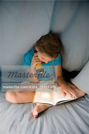 Girl reading under the covers with flashlight Stock Photo - Premium Royalty-Free, Image code: 6106-05410276