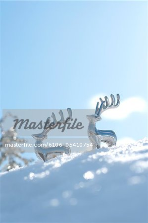 Reindeer shaped metal ornaments on snowy field Stock Photo - Premium Royalty-Free, Image code: 6106-05410754