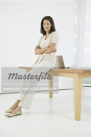 Confident Hispanic Business woman in office Stock Photo - Premium Royalty-Free, Image code: 6106-05411534