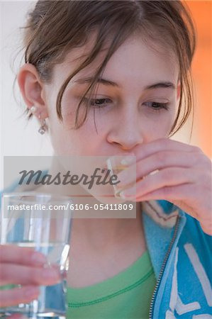 Teenage girl taking medicine Stock Photo - Premium Royalty-Free, Image code: 6106-05411809