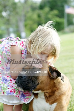 young irl kissing dog on head Stock Photo - Premium Royalty-Free, Image code: 6106-05426938