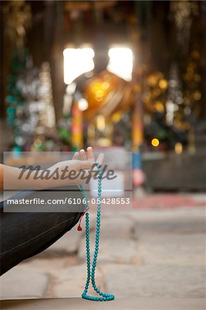 Person meditating with mala, Buddhist prayer beads Stock Photo - Premium Royalty-Free, Image code: 6106-05428553