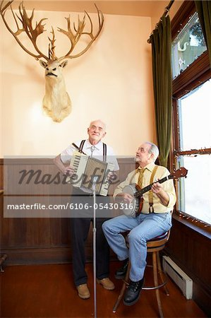 Two man band performing with deer head Stock Photo - Premium Royalty-Free, Image code: 6106-05430316