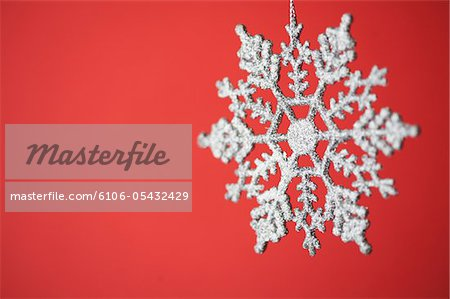 Snowflake Christmas ornament on red background Stock Photo - Premium Royalty-Free, Image code: 6106-05432429