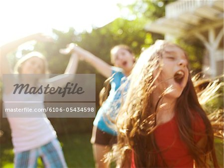 three young girls singing and dancing Stock Photo - Premium Royalty-Free, Image code: 6106-05434598